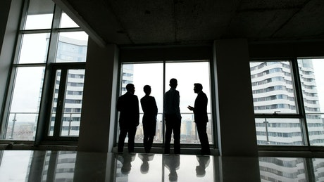 Silhouette of business people talking by highrise window