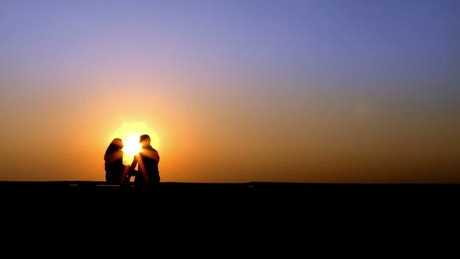 Silhouette of lovers chatting on the skyline at sunset