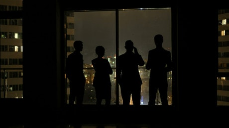 Silhouette of people talking by night view of city