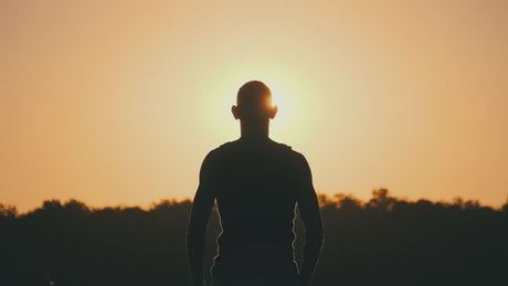 Silhouette of person raising hands against sunset