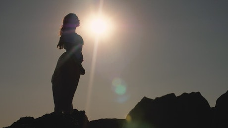 Silhouette of woman holding the sun