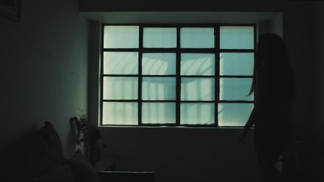 Silhouette of woman opening a window