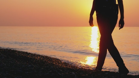 Silhouette of woman walking on the beach at sunset