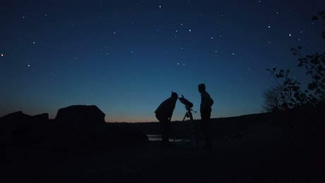 Silhouettes of a couple of men and a telescope