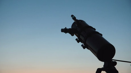 Silhouettes of a man and a boy with a telescope