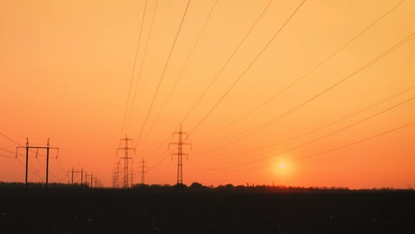 Silhouettes of electric power lines and towers
