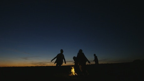 Silhouettes of people in the campfire