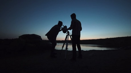 Silhouettes of people using a telescope at dusk