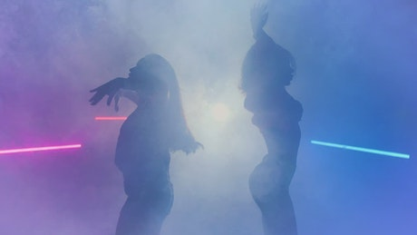 Silhouettes of two dancers under smoke and colored lights