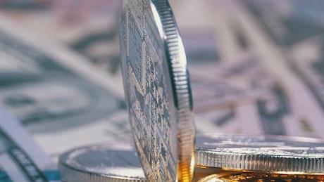 Silver Bitcoin rotating of a dollar bills