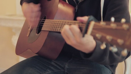 Sitting down and playing a guitar