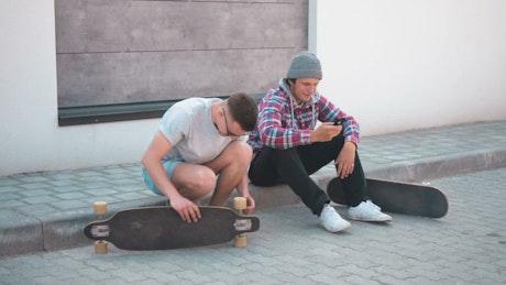 Skateboarder fixing his board