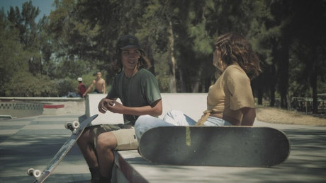 Skateboarder talks with a girl and goes down to the bowl