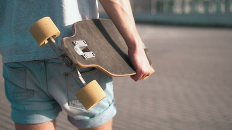 Skateboarder walking with his skateboard