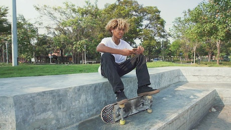 Skater sitting in a park listening to music