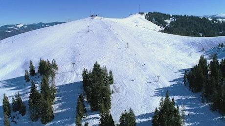 Ski area on a snowy mountain with few trees