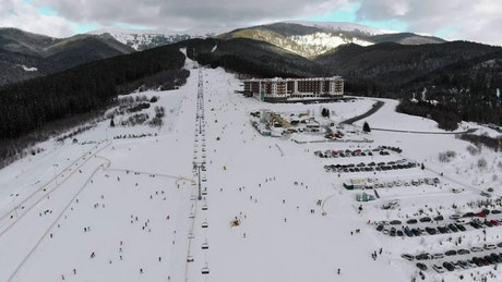 Ski resort and skiers going down the mountain