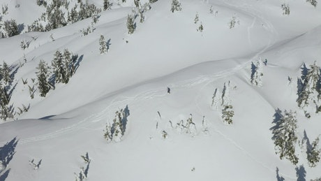 Skier going down a snowy slope