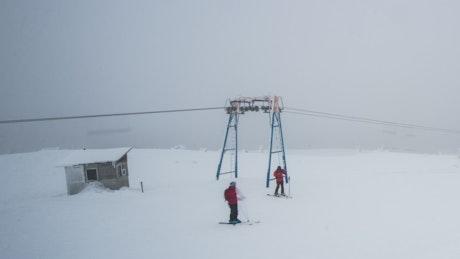Skiers on a misty snowy mountain