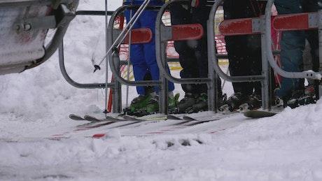 Skiers passing turnstile gate of ski lift entrance