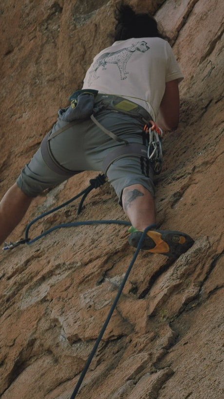 Skilled and experienced mountaineer climbing a rocky mountain