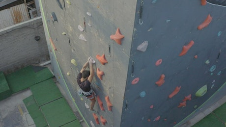Skilled mountaineer climbing a wall outdoors