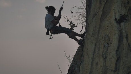 Skilled mountaineer descending from a mountain with a rope