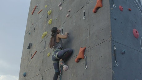 Skillful woman climbing a high wall for mountaineering
