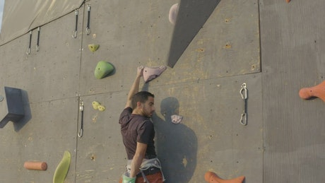 Skillfully climbing to the top of a large mountaineering wall