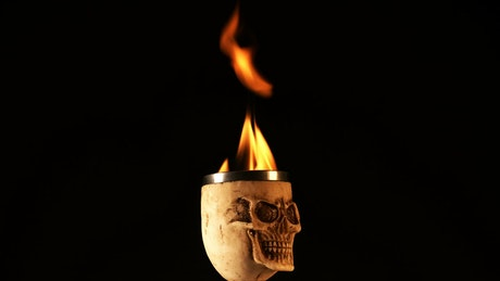 Skull-shaped cup with fire on black background
