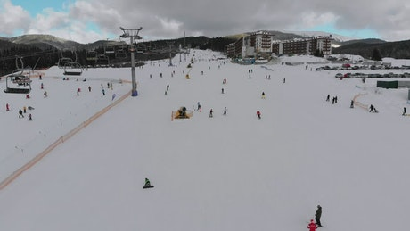 Sky lift and skiers in the snowy mountain
