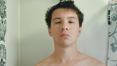 Sleepy man taking a shower