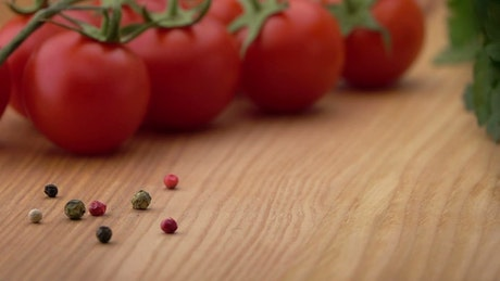 Sliced tomato falls on a wooden board