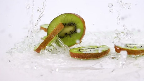 Slices of kiwi falling into water