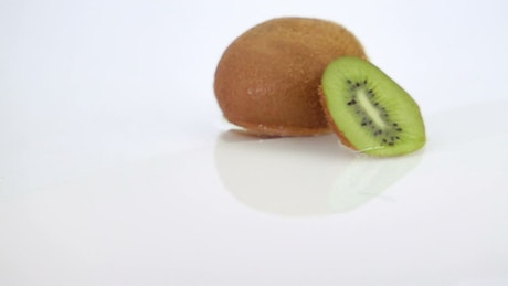 Slices of kiwi falling over water