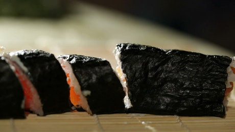 Slicing up a roll of Sushi