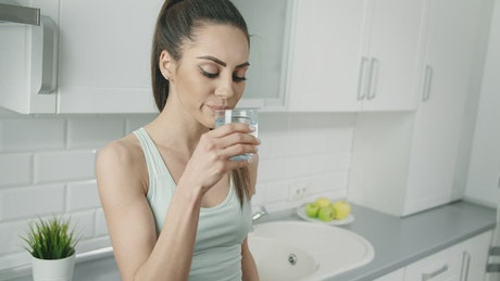Slim woman sips water and smiles in kitchen