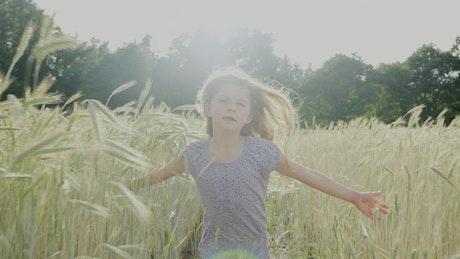 Slow motion girl running through tall grass in sun