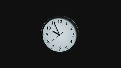 Slowly approaching a clock on a black background