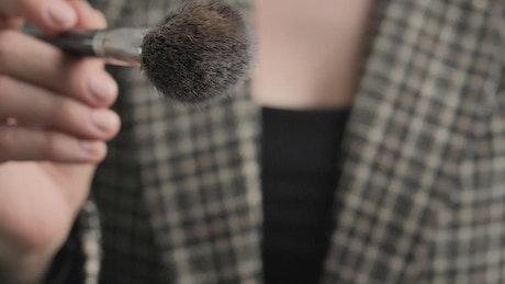Slowly shaking a powder makeup brush