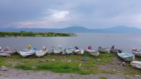 Small boats on the shore of a huge lake