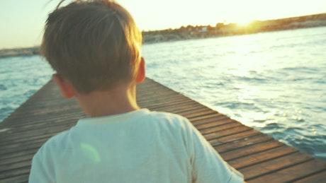 Small boy running along a pier