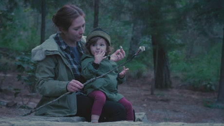 Small family eating roasted marshmallows in nature