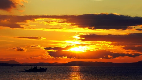 Small fishing boat crossing the sunset