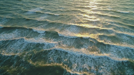 Small frequent waves reaching the beach, high view
