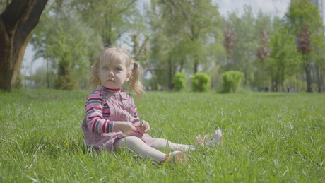 Small girl sitting in grass and pointing