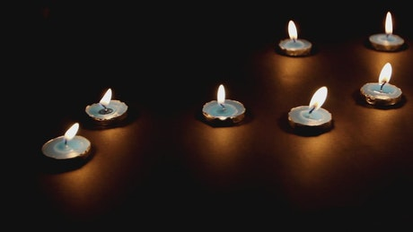 Small lit candles in the dark