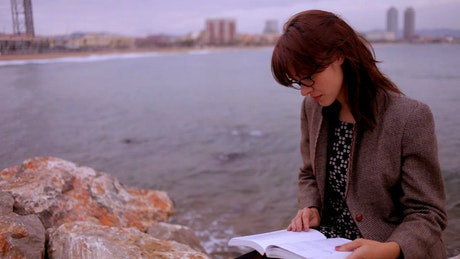 Smart woman reading by the sea