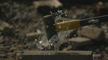 Smashing a glass bottle with a sledge