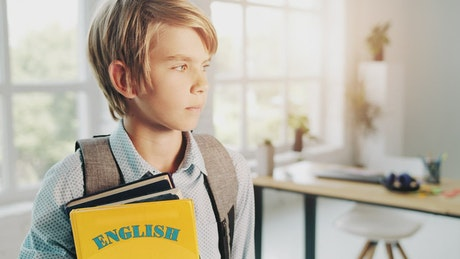 Smiling boy holds English education book in bright room